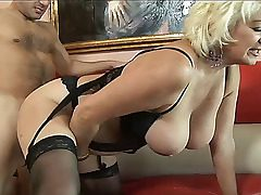 Old slut in undergarments with floppy breasts fucks a young stud. She sucks his cock and gets a doggystyle creampie